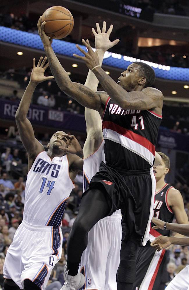 Portland Trail Blazers' Thomas Robinson gets his shot off over the defense of Charlotte Bobcats' Michael Kidd-Gilchrist, left and Cody Zeller, behind, during the second half of an NBA basketball game in Charlotte, N.C., Saturday, March 22, 2014. The Bobcats won 124-94
