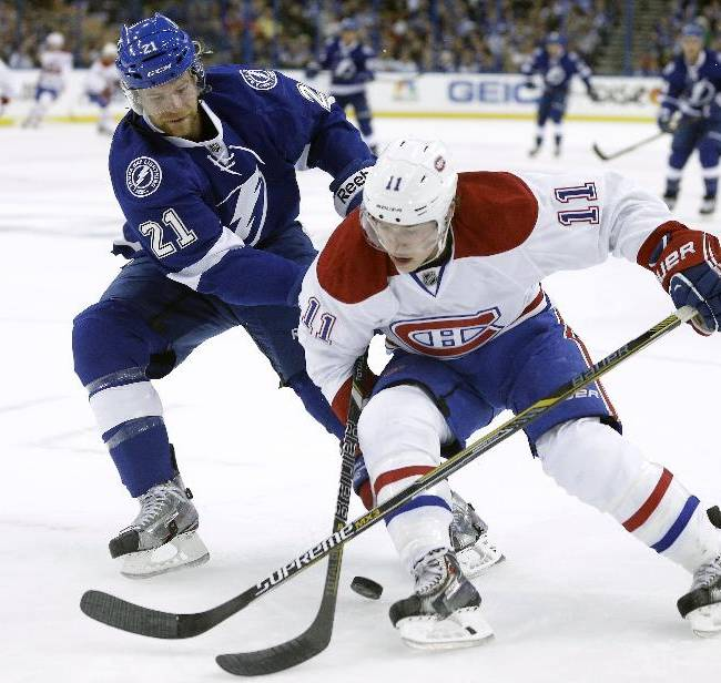 Tampa Bay Lightning defenseman Mike Kostka (21) battles with Montreal Canadiens right wing Brendan Gallagher (11) for a loose puck during the first period of Game 1 of a first-round NHL hockey playoff series on Wednesday, April 16, 2014, in Tampa, Fla