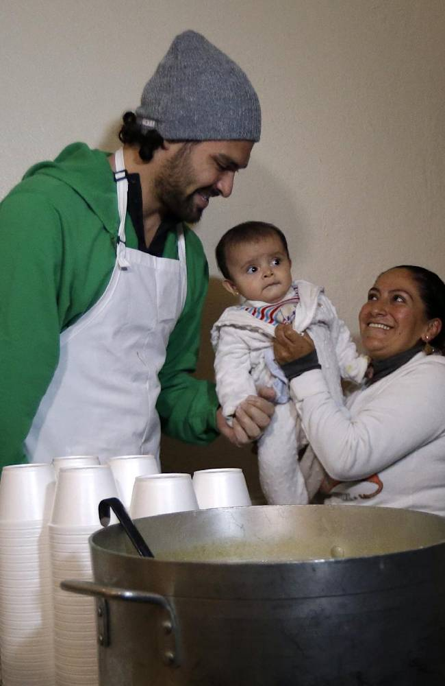 New York Jets NFL football quarterback Mark Sanchez, left, talks to Yolanda Chimborazo, right, and 6-month-old Ailyn Saeteros during a visit to the Community Soup Kitchen of Morristown as part of the team's Thanksgiving Day week celebration, Tuesday, Nov. 26, 2013, in Morristown, N.J