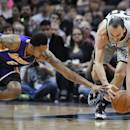 San Antonio Spurs guard Manu Ginobili, right, comes up with a loose ball in front of Los Angeles Lakers guard Kent Bazemore during the first half of an NBA basketball game Friday, March 14, 2014. (AP Photo/Bahram Mark Sobhani)