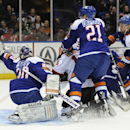 New Jersey Devils' Adam Henrique (14) shoots the puck past New York Islanders goalie Evgeni Nabokov (20) as Islanders' Kyle Okposo (21) and Calvin de Haan (44) watch from behind in the first period of an NHL hockey game on Saturday, March 1, 2014, in Uni