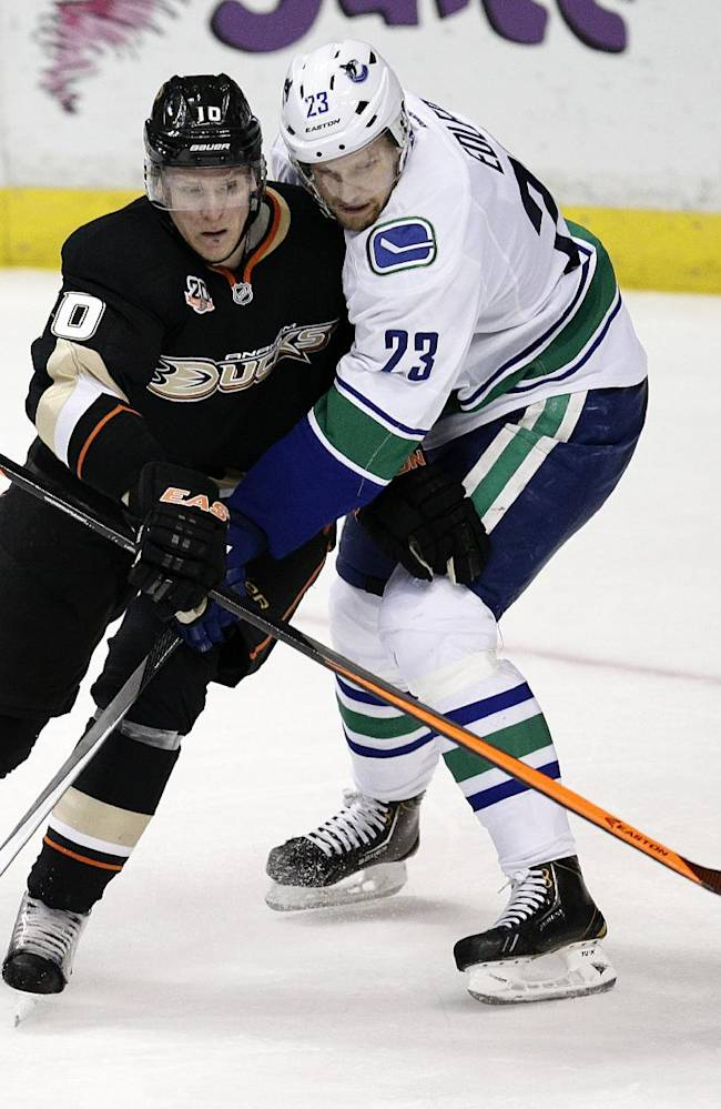 Anaheim Ducks' Corey Perry, left, shoots to score as he is defended by Vancouver Canucks' Alexander Edler during the third period of an NHL hockey game on Wednesday, Jan. 15, 2014, in Anaheim, Calif. The Ducks won 9-1