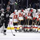 CORRECTS TO OVERTIME Members of the Calgary Flames, right, celebrate as member of the Los Angeles Kings skate off the ice after Flames' defenseman Mark Giordano scored a game-winning goal during overtime of an NHL hockey game, Monday, Dec. 22, 2014, in Los Angeles. The Flames won 4-3 in overtime. (AP Photo/Mark J. Terrill)