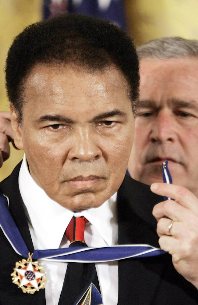 In this Nov. 9, 2005 file photo, President Bush presents the Presidential Medal of Freedom to boxer Muhammad Ali in the East Room of the White House. He is now so much a part of the nation's social fabric that it's hard to comprehend a time when Ali was more reviled than revered