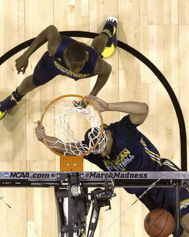 Michigan's Jordan Morgan dunks as Caris LeVert watches during practice for their NCAA Midwest Regional semifinal college basketball tournament game Thursday, March 27, 2014, in Indianapolis. Michigan plays Tennessee on Friday, March 28, 2013