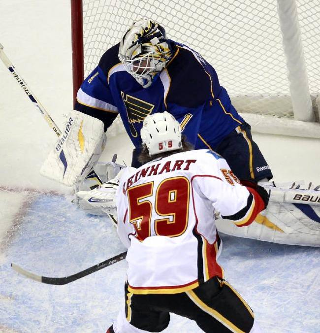 St. Louis Blues goalie Brian Elliott, top, deflects the puck as Calgary Flames' Max Reinhart watches during the second period of an NHL hockey game Thursday, Nov. 7, 2013, in St. Louis