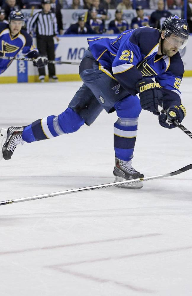 Boston Bruins' Brad Marchand, left, falls to the ice as St. Louis Blues' Patrik Berglund, Sweden, reaches for a loose puck during the first period of an NHL hockey game Thursday, Feb. 6, 2014, in St. Louis