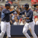 Tampa Bay Rays Sean Rodriguez is greeted by Yunel Escobar after scoring on a double by Jose Molina in the third inning of an exhibition baseball game against the Boston Red Sox in Port Charlotte, Fla., Tuesday, March 25, 2014. The Red Sox won 4-2 The Asso