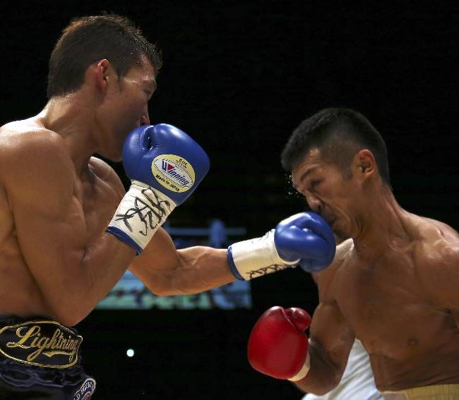 Japanese champion Takashi Uchiyama, right, takes a left from compatriot challenger Daiki Kaneko in the second round of their WBA super featherweight boxing title bout in Tokyo, Tuesday, Dec. 31, 2013. Uchiyama defended his title by a unanimous decision