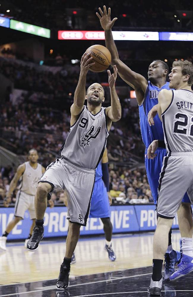 San Antonio Spurs' Tony Parker (9), of France, shoots around Dallas Mavericks' Samuel Dalembert, center, during the first half of an NBA basketball game, Sunday, March 2, 2014, in San Antonio