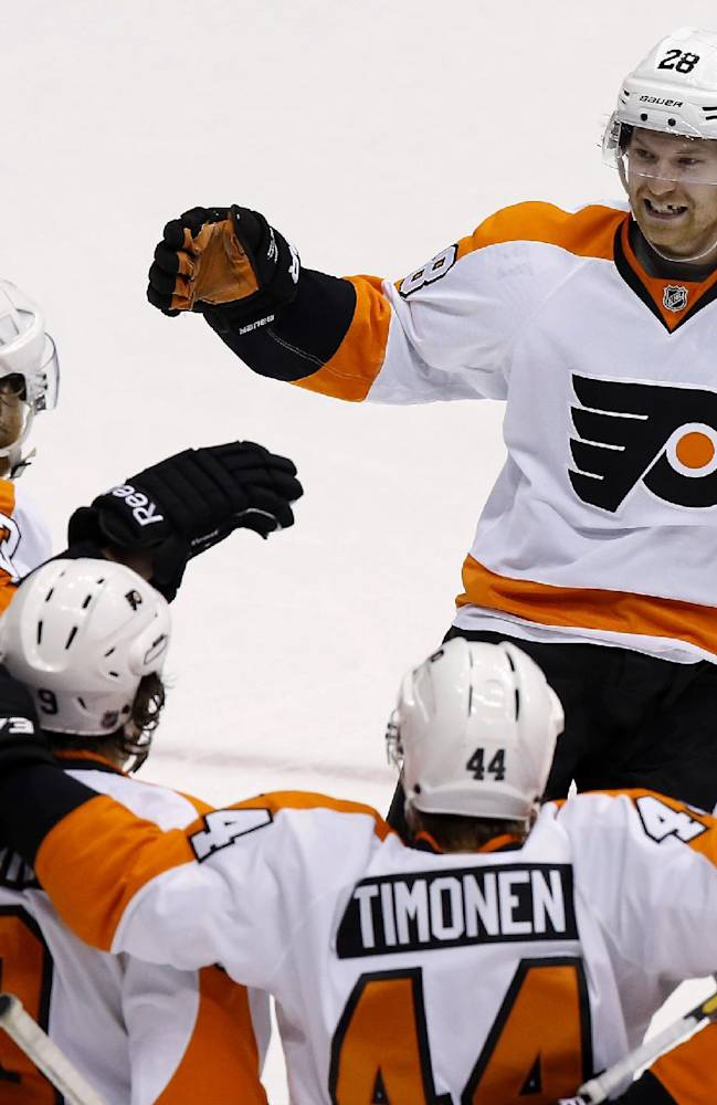 Philadelphia Flyers' Claude Giroux (28) smiles as he arrives to join the celebration of a goal by Jakub Voracek (93), of the Czech Republic, against the Phoenix Coyotes, with teammates Braydon Coburn (5), Kimmo Timonen (44), of Finland, and Steve Downie (9) during the third period of an NHL hockey game Saturday, Jan. 4, 2014, in Glendale, Ariz. The Flyers defeated the Coyotes 5-3