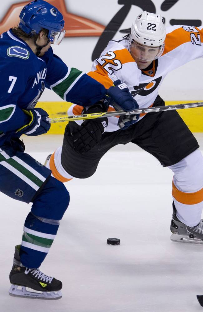 Vancouver Canucks left wing David Booth (7) fights for control of the puck with Philadelphia Flyers defenceman Luke Schenn (22) during the second period of an NHL hockey game in Vancouver, British Columbia, Monday, Dec. 30, 2013