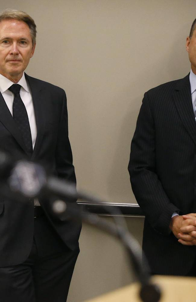 New Pittsburgh Penguins head coach Mike Johnston, left, and new assistant coach Rick Tocchet, right, listen before they are introduced at a news conference as the NHL hockey teams new coaches on Wednesday, June 25, 2014 in Pittsburgh