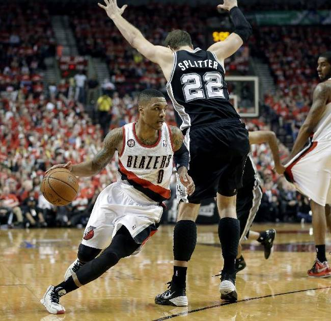 Portland Trail Blazers' Damian Lillard (0) drives around San Antonio Spurs' Tiago Splitter (22) in the second quarter during Game 3 of a Western Conference semifinal NBA basketball playoff series, Saturday, May 10, 2014, in Portland, Ore