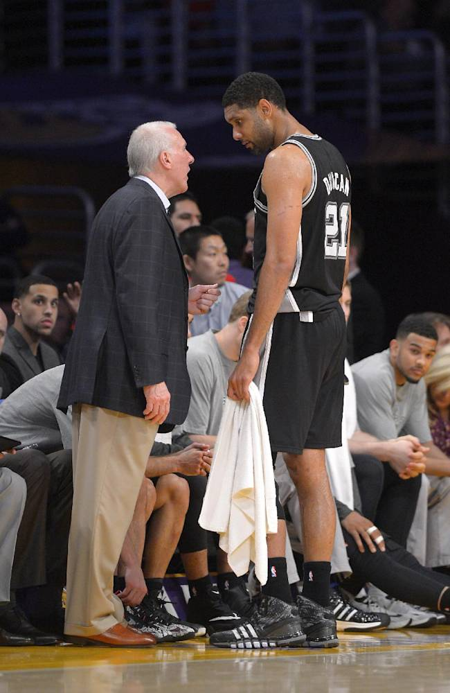 San Antonio Spurs forward Tim Duncan, right, talks with head coach Gregg Popovich during the second half of their NBA basketball game against the Los Angeles Lakers, Wednesday, March 19, 2014, in Los Angeles. The Spurs won 125-109