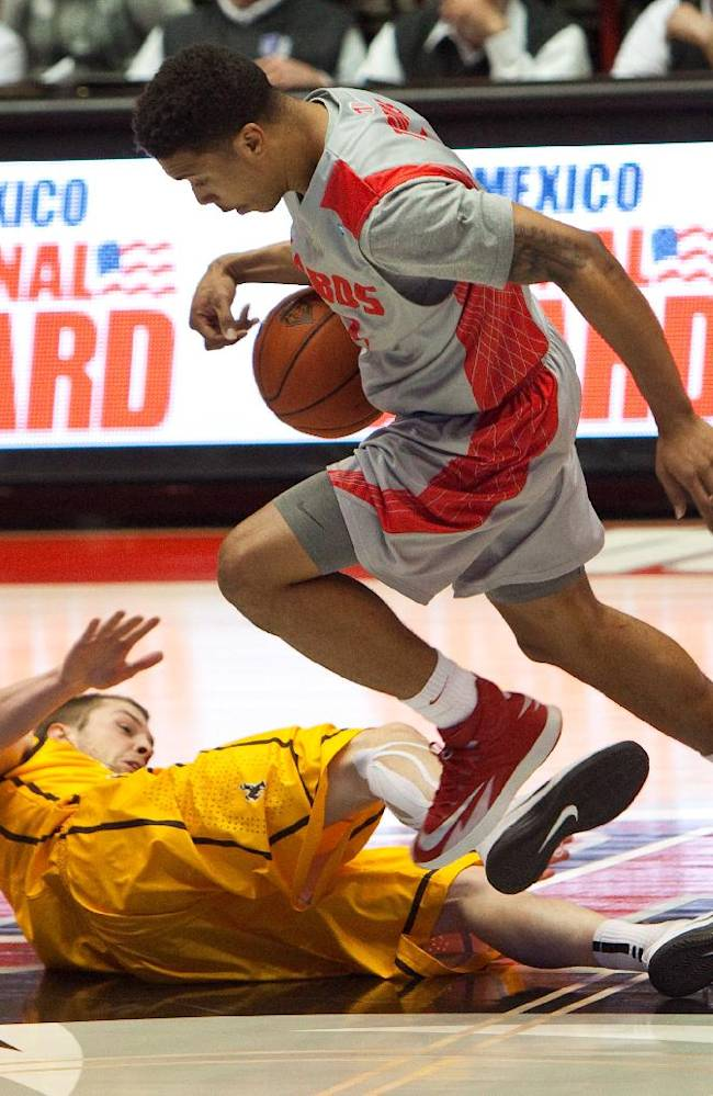 New Mexico's Cleveland Thomas grabs a loose ball from Wyoming's Nathan Sobey in the second half of an NCAA college basketball game Wednesday, Feb. 5, 2014 in Albuquerque, N.M. New Mexico won in overtime 66-61