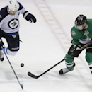 Dallas Stars center Tyler Seguin (91) an Winnipeg Jets defenseman Mark Stuart (5) position for control of the puck during the third period of an NHL hockey game Monday, March 24, 2014, in Dallas. The Stars won 2-1 The Associated Press