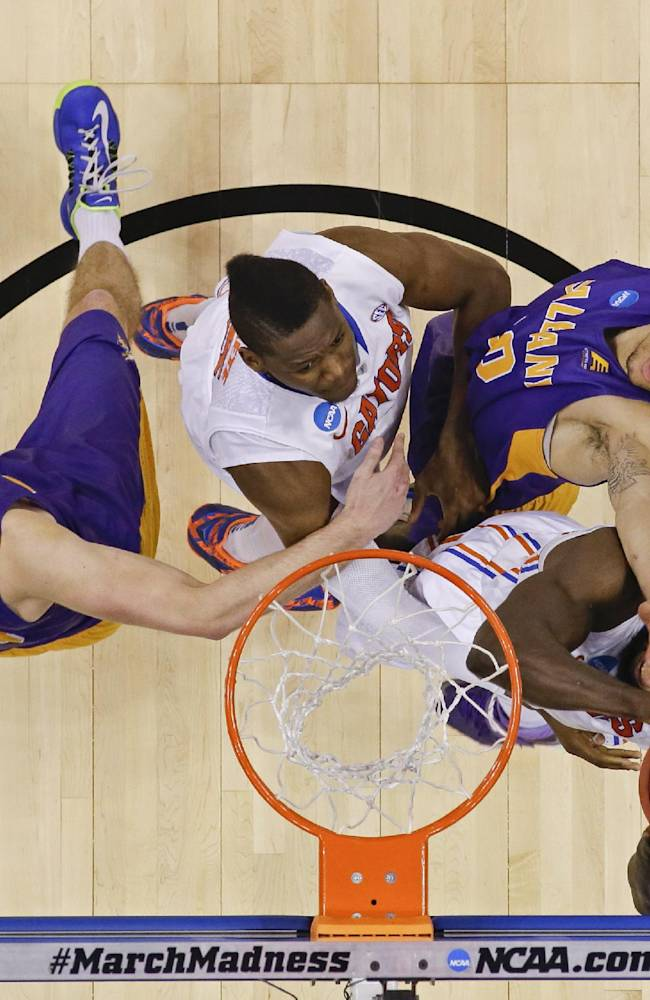 Florida center Patric Young, right, grabs a rebound as Albany center John Puk, left, and forward Gary Johnson, second from right, go against him as teammate Florida forward Will Yeguete, second from left, comes in to help in the second half of a second-round game of the NCAA college basketball tournament in Orlando, Fla., Thursday, March 20, 2014