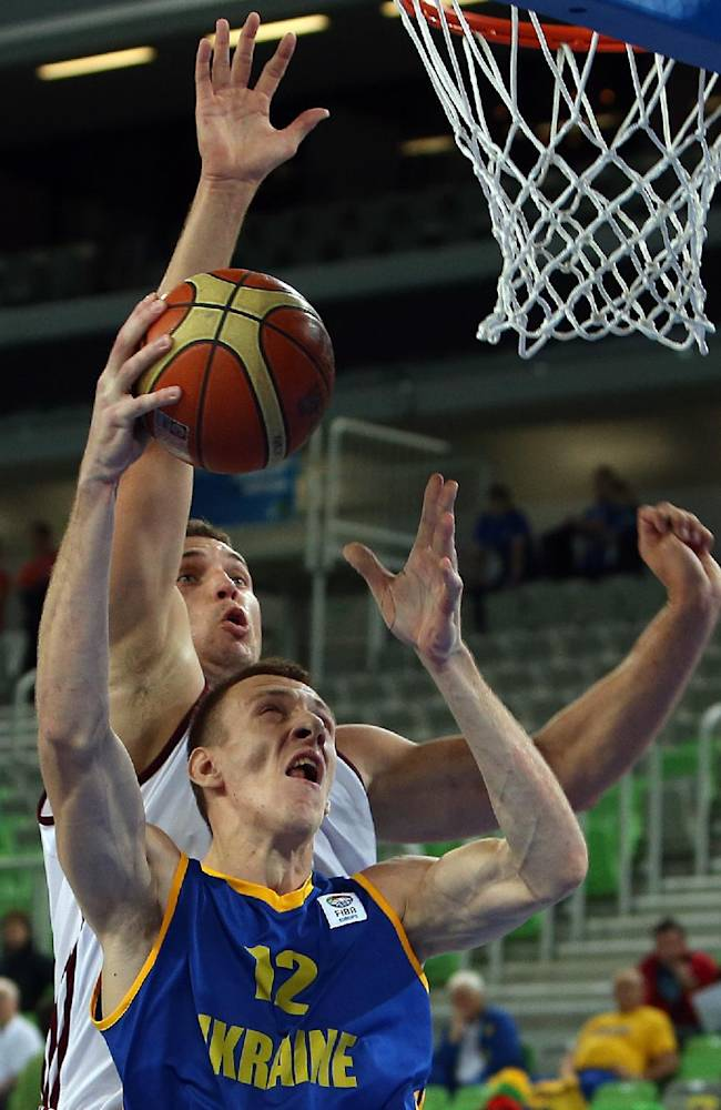 Latvia's Andrejs Selakovs, rear, and Ukraine's Maxim Korniyenko jump for the rebound during their EuroBasket European Basketball Championship Group E match at the Stozice Arena, in Ljubljana, Slovenia, Wednesday, Sept. 11, 2013