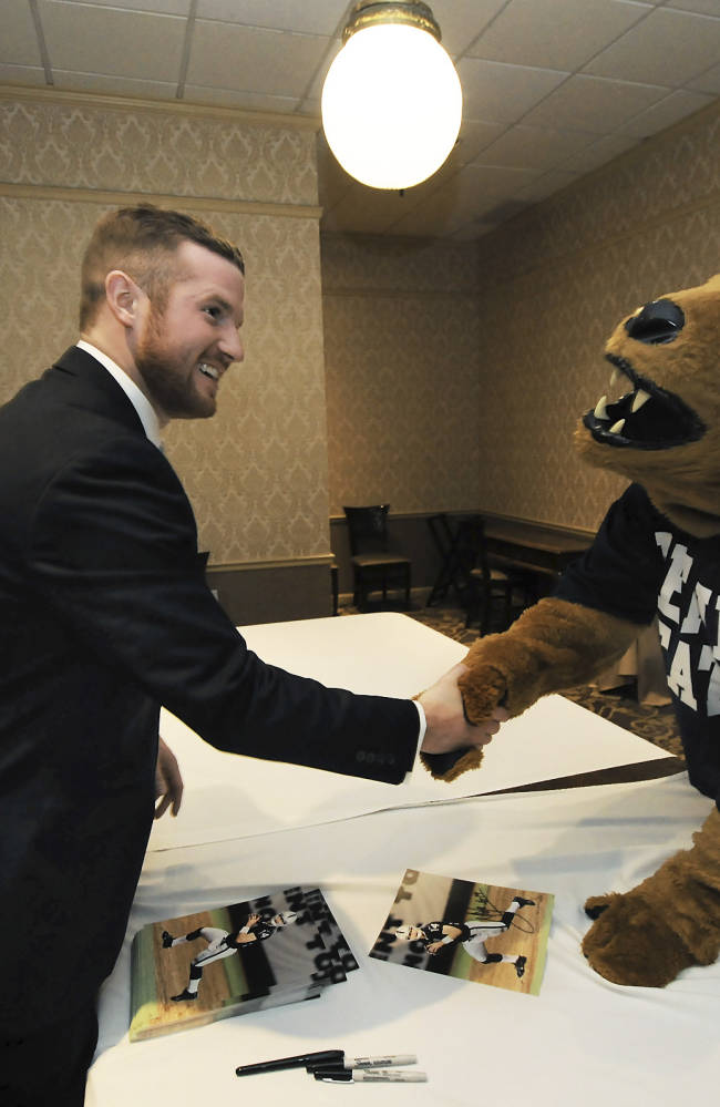 Oakland Raiders quarterback Matt McGloin receives a handshake form and gives an autograph picture to the Penn State Nittany Lion mascot Thursday, Feb. 20, 2014, during a banquet held in honor of McGloin, a native of Scranton, Pa., and a former Penn State quarterback