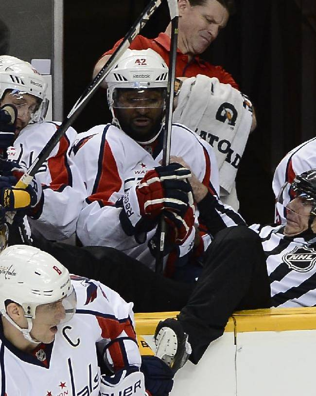 Linesman Brad Lazarowich, right, falls into the Washington Capitals bench after Capitals right wing Alex Ovechkin (8), of Russia, checked Nashville Predators forward Mike Fisher (12) into the boards in the second period of an NHL hockey game on Sunday, March 30, 2014, in Nashville, Tenn