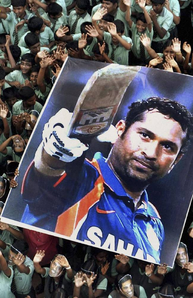 In this March 16, 2012 file photo, Indian students hold a large poster of Indian cricketer Sachin Tendulkar after Tendulkar batted for his landmark 100th century, at a school in Chennai, southern India. Tendulkar, the most prolific batsman in international cricket history, plays his 200th and last test for India against West Indies from Thursday, Nov. 14. (AP Photo, File)