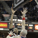 Sacramento Kings forward Rudy Gay, left, scores the game-tying basket over Washington Wizards' Marcin Gortat,center, of Poland, and Trevor Ariza, right, with five seconds left in the fourth quarter of an NBA basketball game in Sacramento, Calif., Tuesday