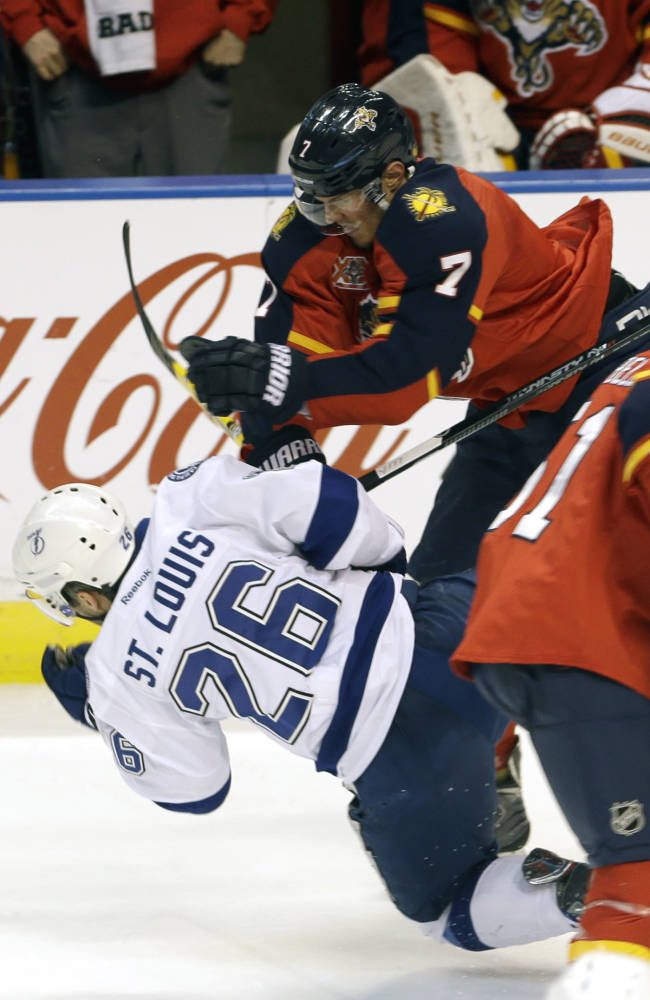 Florida Panthers defenseman Dmitry Kulikov (7) checks Tampa Bay Lightning right wing Martin St. Louis (26) during the first period of an NHL hockey game in Sunrise, Fla., Monday, Dec. 23, 2013