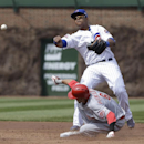 Chicago Cubs shortstop Starlin Castro, top, throws out Cincinnati Reds' Joey Votto at first base base after forcing out Billy Hamilton during the third inning of a baseball game in Chicago, Saturday, April 19, 2014 The Associated Press