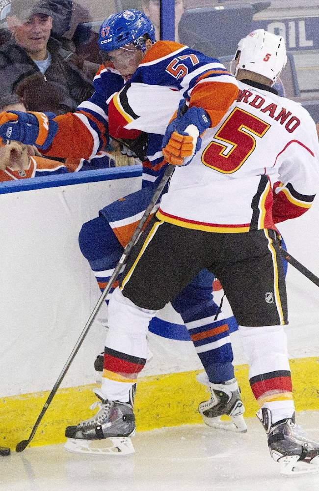 Calgary Flames' Mark Giordano (5) checks Edmonton Oilers' David Perron (57) during the second period of an NHL hockey game Saturday, March 1, 2014, in Edmonton, Alberta