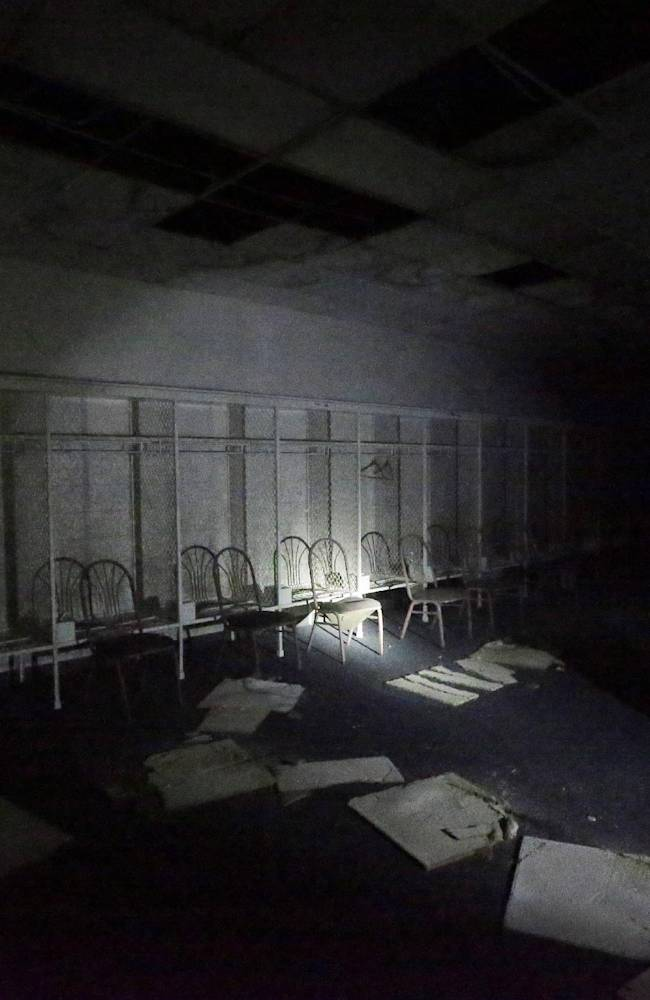 In this May 12, 2014 photo, a light shines in the area of Barry Sanders' locker inside the Pontiac Silverdome in Pontiac, Mich. The venue is a shell of its former self with its roof in tatters and a lack of electrical power that has left the stadium's innards dark and mold-covered. The Silverdome's current owner is determined to cash in before it's too late, putting everything inside up for auction starting on Wednesday, May 21
