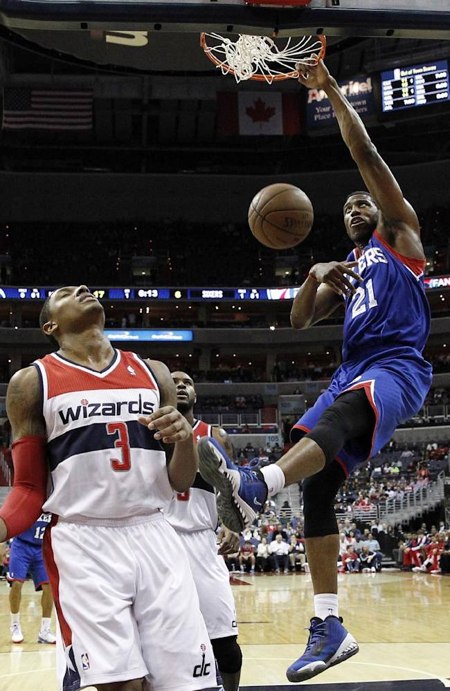 Philadelphia 76ers forward Thaddeus Young (21) dunks over Washington Wizards guard Bradley Beal (3) and forward Trevor Booker (35) in the first half of an NBA basketball game, Friday, Nov. 1, 2013, in Washington