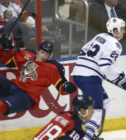 After slamming into Toronto Maple Leafs' Jerred Smithson (22), Florida Panthers' Dmitry Kulilov (7) is knocked to the ice during the first period of an NHL hockey game in Sunrise, Fla., Tuesday, Feb. 4, 2014. (AP Photo/J Pat Carter)
