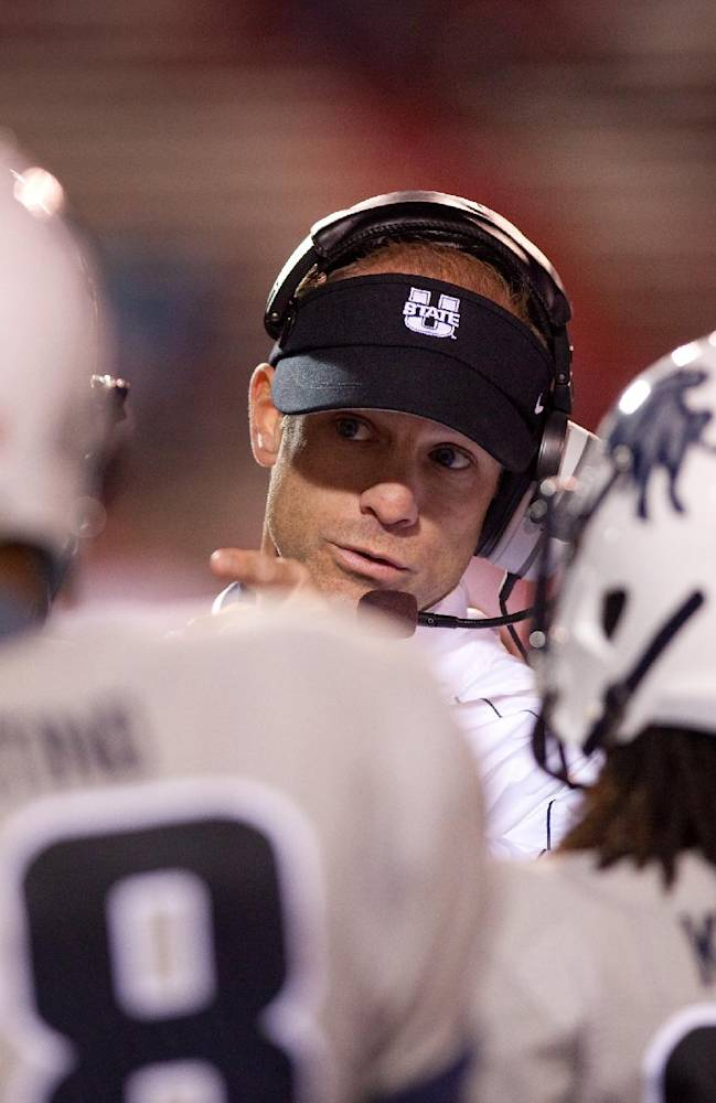 Utah State head coach Matt Wells talks to his team during the second half of an NCAA college football game against New Mexico, Saturday, Oct. 19, 2013, at University Stadium in Albuquerque, N.M. Utah State won 45-10