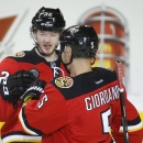 Calgary Flames' Paul Byron, left, celebrates his goal with teammate Mark Giordano during the second period of an NHL hockey game against the Ottawa Senators on Wednesday, March 5, 2014, in Calgary, Alberta The Associated Press