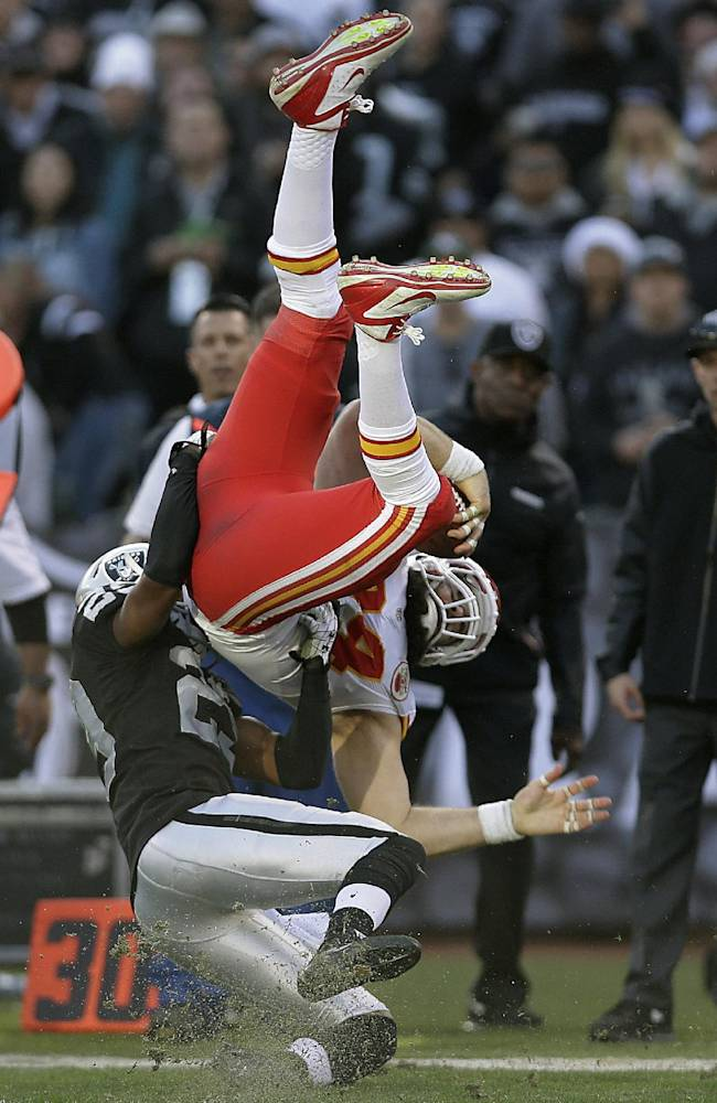 Kansas City Chiefs tight end Sean McGrath, top, is tackled by Oakland Raiders cornerback Brandian Ross during the third quarter of an NFL football game in Oakland, Calif., Sunday, Dec. 15, 2013