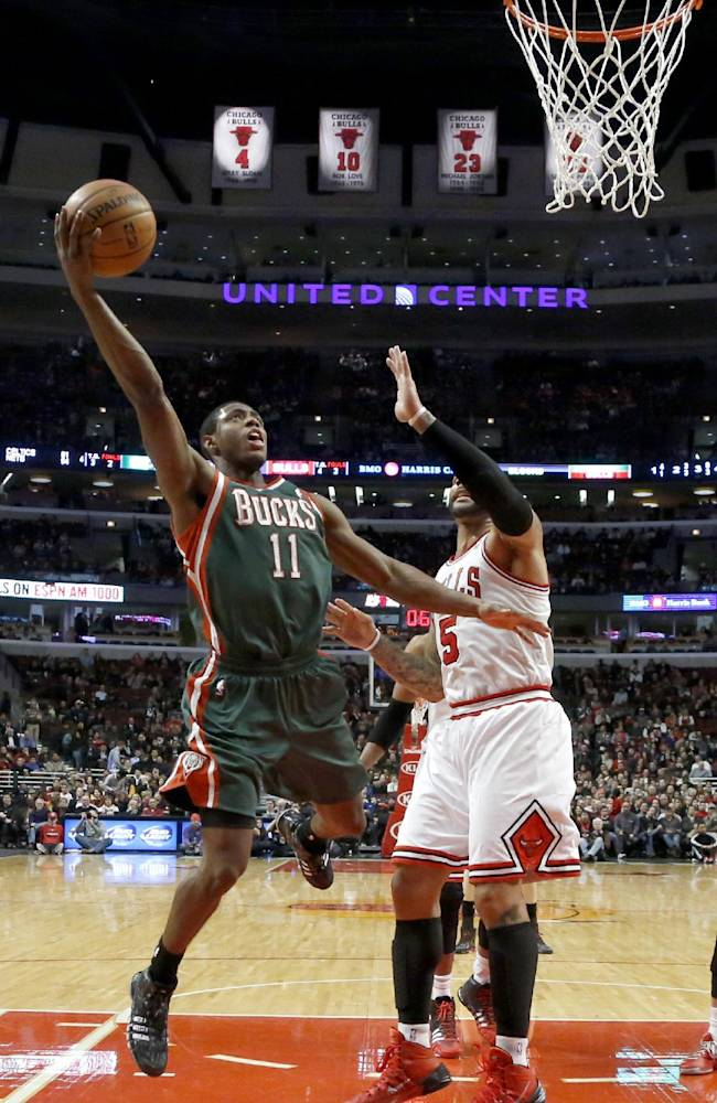 Milwaukee Bucks point guard Brandon Knight (11) drives and scores past Chicago Bulls forward Carlos Boozer (5) during the second half of an NBA basketball game Tuesday, Dec. 10, 2013, in Chicago. The Bucks won 78-74