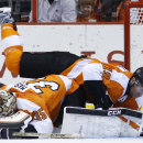 Philadelphia Flyers' Scott Hartnell, top, lands on goalie Steve Mason during the second period of an NHL hockey game against the Boston Bruins, Sunday, March 30, 2014, in Philadelphia The Associated Press