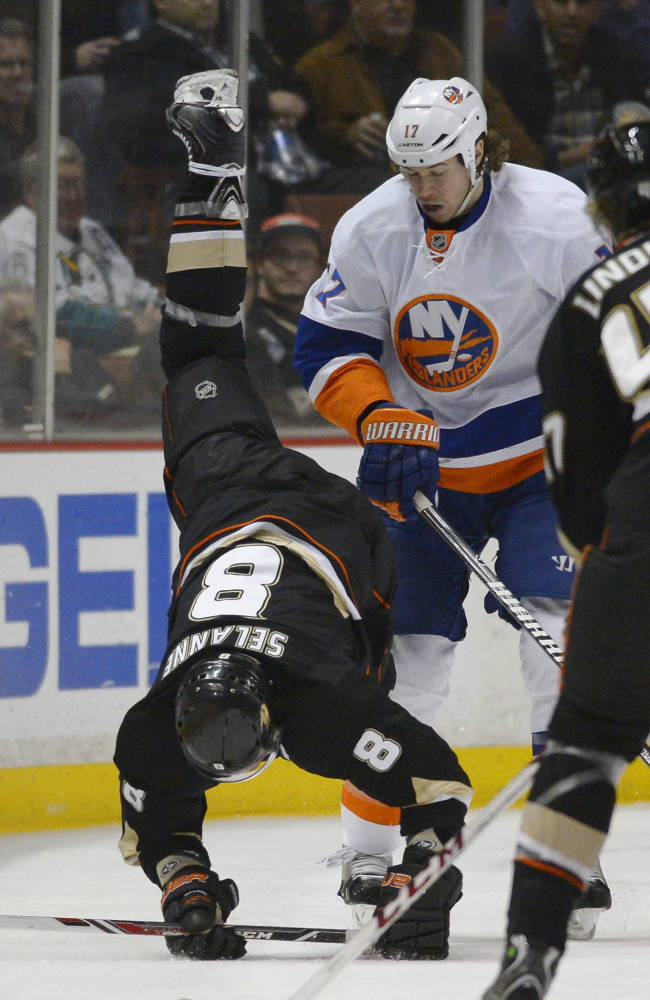 Anaheim Ducks right wing Teemu Selanne, below, of Finland, falls to the ice after being pushed from behind by New York Islanders left wing Matt Martin during the third period of an NHL hockey game, Monday, Dec. 9, 2013, in Anaheim, Calif. The Ducks won 5-2