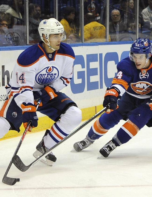 New York Islanders' Thomas Hickey (14) tries to drive the puck away from Edmonton Oilers' Jordan Eberle (14) in the first period of an NHL hockey game on Thursday, Oct. 17, 2013, in Uniondale, N.Y. The Islanders won 3-2