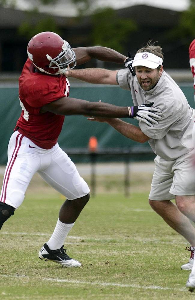 Alabama defensive coordinator/secondary coach Kirby Smart, right, shows proper technique for a drill with Alabama defensive back Jarrick Williams during an NCAA college spring football practice, Monday, April 7, 2014, in Tuscaloosa, Ala