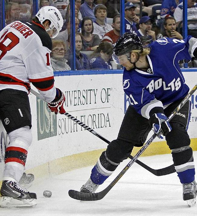 Tampa Bay Lightning defenseman Mike Kostka (21) and New Jersey Devils right wing Steve Bernier (18) vie for the puck during the first period of an NHL hockey game Saturday, March 15, 2014, in Tampa, Fla. The Lightning won 3-0