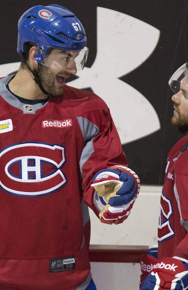 Montreal Canadiens' Max Pacioretty, left, chats with teammate David Desharnais during NHL hockey practice Wednesday, April 30, 2014, in Brossard, Quebec. The Canadiens face the Boston Bruins in Game 1 in the second round of the Stanley Cup playoffs Thursday in Boston