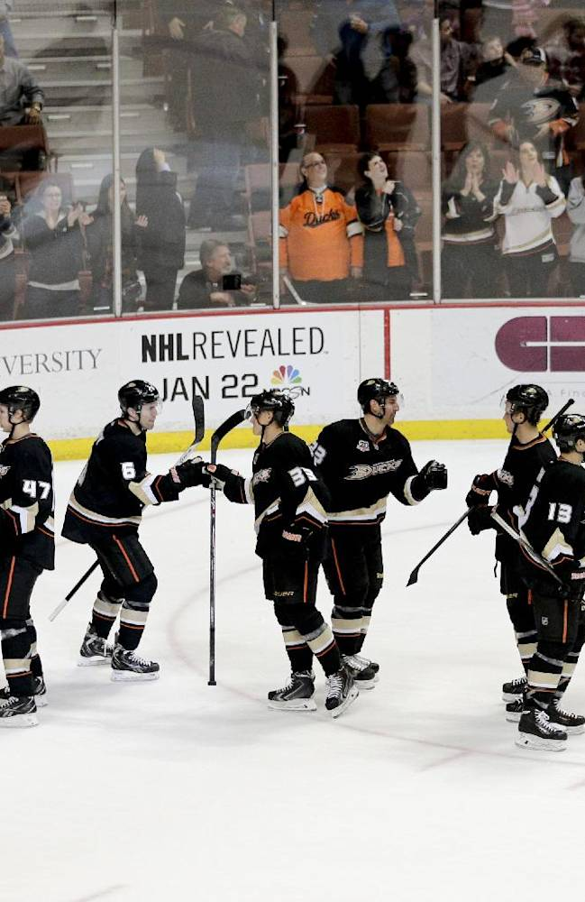 The Anaheim Ducks players celebrate their 9-1 win against the Vancouver Canucks after an NHL hockey game on Wednesday, Jan. 15, 2014, in Anaheim, Calif