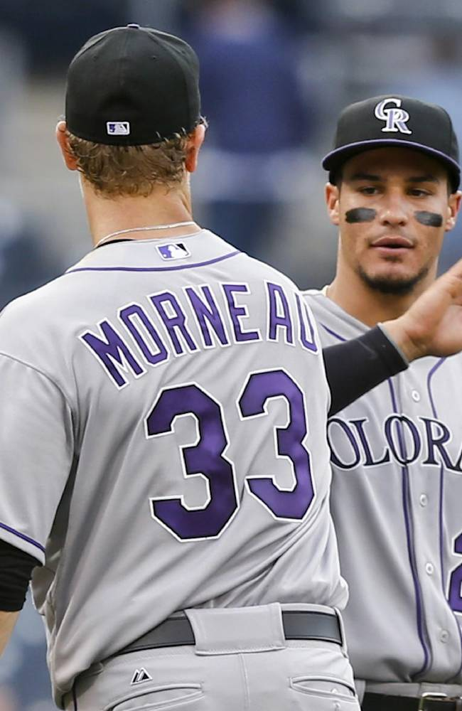 Colorado Rockies' Justin Morneau and Nolan Arenado slap high-fives after the Rockies finished off a 3-1 victory over the San Diego Padres in a baseball game Thursday, April 17, 2014, in San Diego