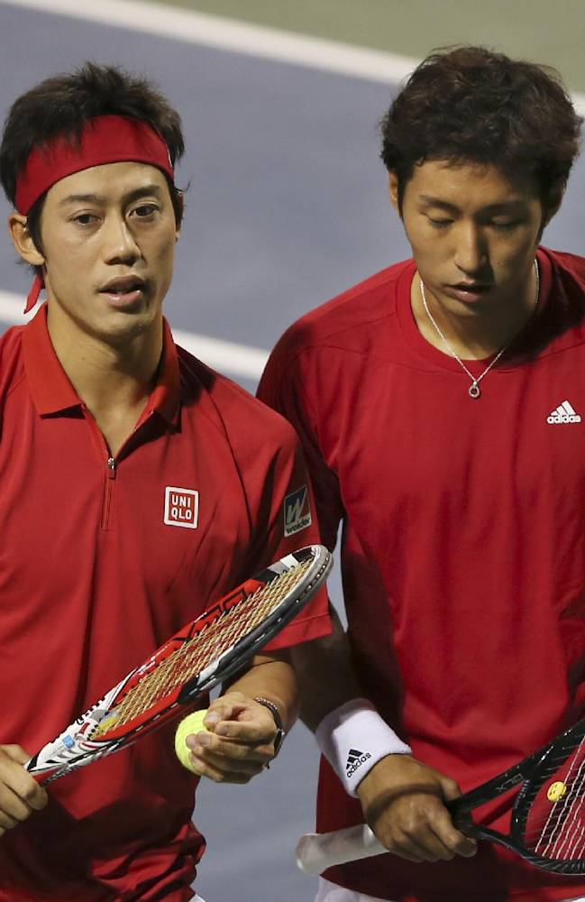 Kei Nishikori of Japan talks with his compatriot Yasutaka Uchiyama during their 1st round of Davis Cup World Group doubles tennis match against Canada in Tokyo, Saturday, Feb. 1, 2014