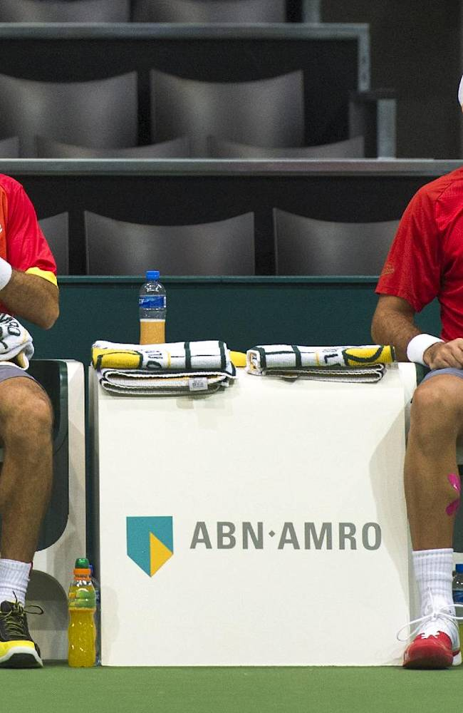 Romanian Horia Tecau, right, and Jean-Julien Rojer of The Netherlands, left, have a break during their game against Michael Llodra and Nicolas Mahut of France at the men's double final, of the 41st ABN AMRO world tennis tournament, at Ahoy Arena,  in Rotterdam, Netherlands, Sunday Feb. 16, 2014