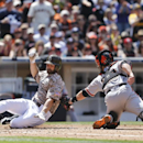 San Francisco Giants catcher Buster Posey, right, makes a swipe tag to San Diego Padres' Xavier Nady who is out trying to score from first on a bases-loaded double hit by Chase Headley in the third inning a baseball game on Sunday, April 20, 2014, in San