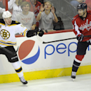 Boston Bruins right wing Reilly Smith (18) reaches for the puck against Washington Capitals right wing Troy Brouwer (20) during the third period of an NHL hockey game, Saturday, March 29, 2014, in Washington. The Bruins won 4-2 The Associated Press