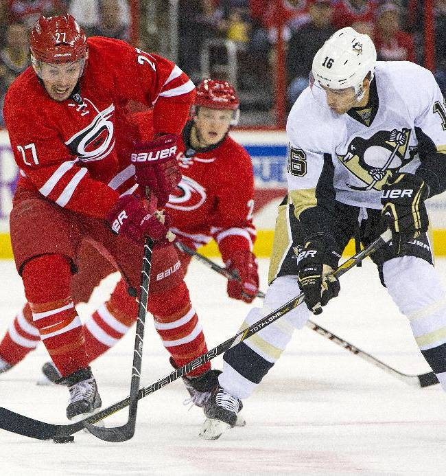 Carolina Hurricanes' Justin Faulk (27) battles with Pittsburgh Penguins' Brandon Sutter (16) during the first period of an NHL hockey game, Friday, Dec. 27, 2013, in Raleigh, N.C